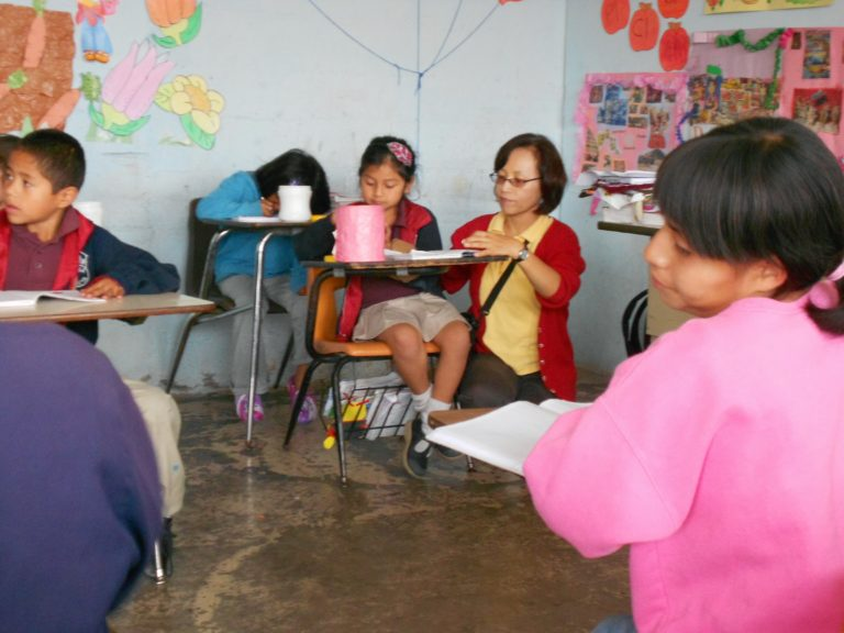 Guatemala Volunteer Teaching at Desk